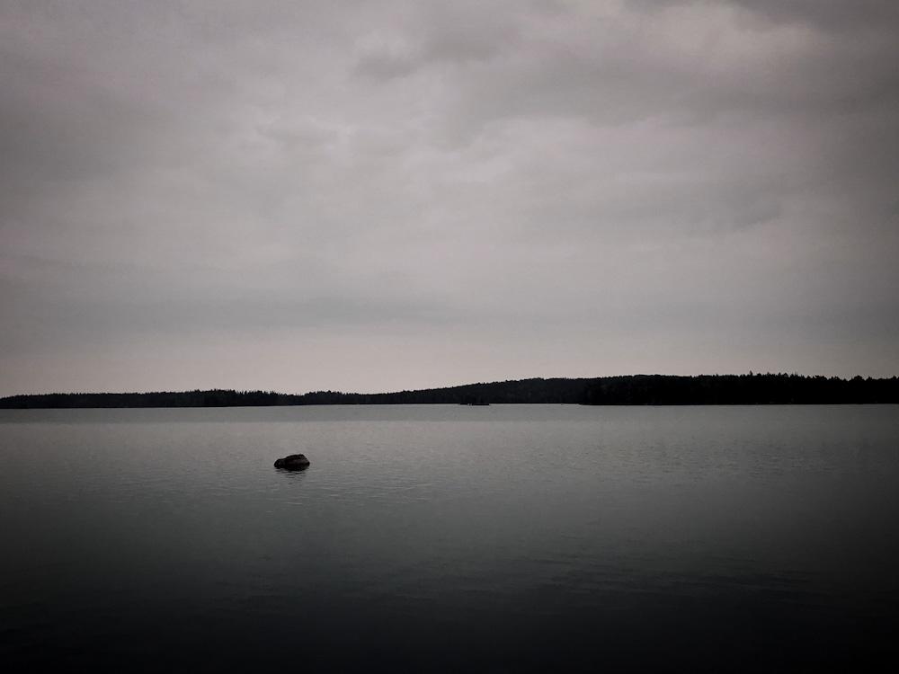 Ein einzelner Stein ragt aus einer glatten Wasseroberfläche