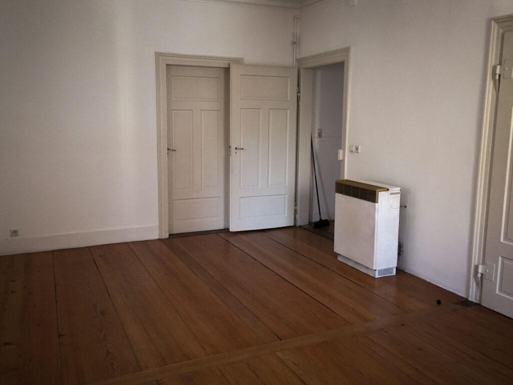 Eine leere Altbauwohnung. An der Wand lehnt ein Besen.