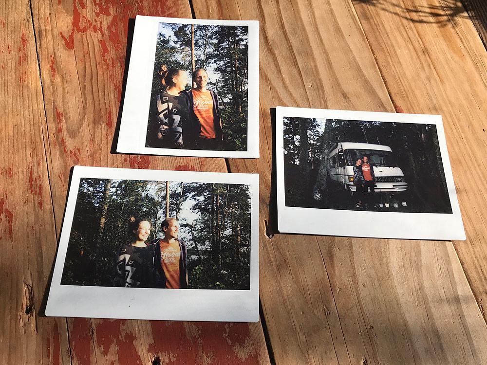 Minimalistisch reisen: Drei Polaroid Fotos liegen auf einem Holztisch