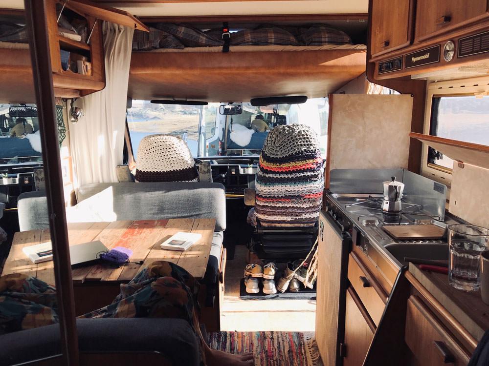 Minimalistisch reisen: Innenansicht eines Wohnmobils. Auf dem Tisch liegt ein Buch und ein Laptop, auf der Küchenarbeitsplatte stehen Gläser und ein Kaffeekocher.