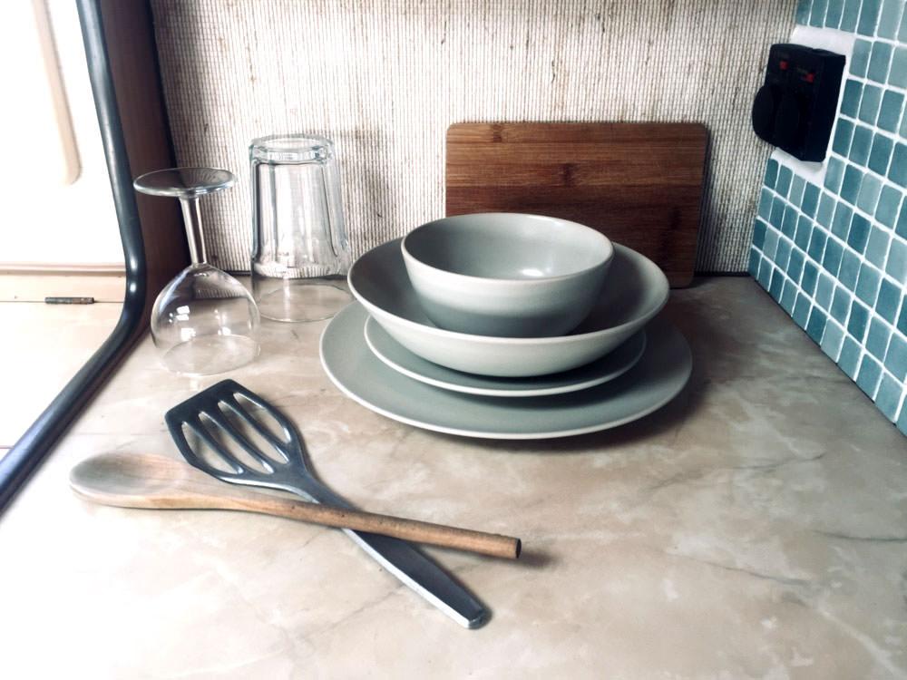 Zero Waste Camper: Gläser, Teller und etwas Kochbesteck liegen auf der Küchenarbeitsplatte