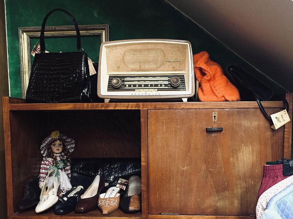 Second Hand Lissabon: Ein Retro-Radio steht auf einer alten Kommode. Daneben befinden sich eine alte Handtasche aus Lackleder und Vintage Damenschuhe.