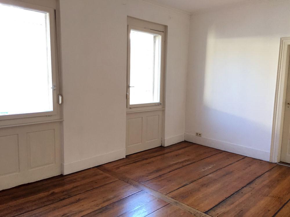 Auf Reise sparen: Ein leeres Zimmer in einer Altbauwohnung. Dielenboden und zwei Fesnter.