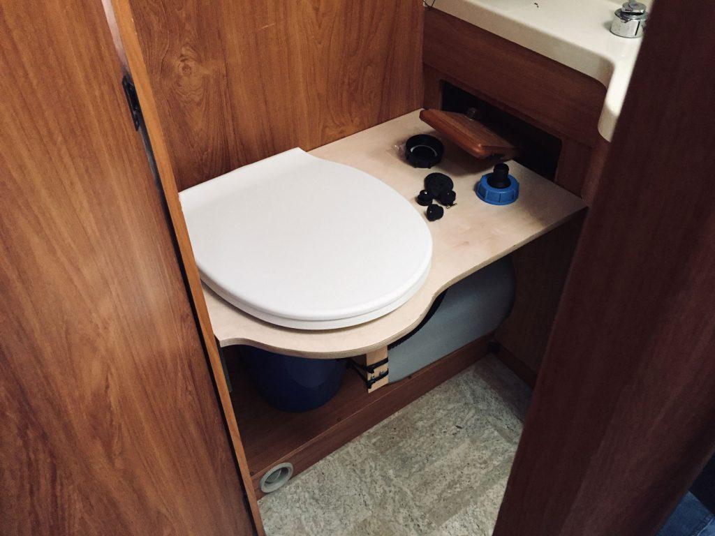Trockentrenntoilette: Eine Klobrille auf einem Holzbrett in einem Camper-Bad. Darunter sind ein Eimer und ein Kanister zu sehen,