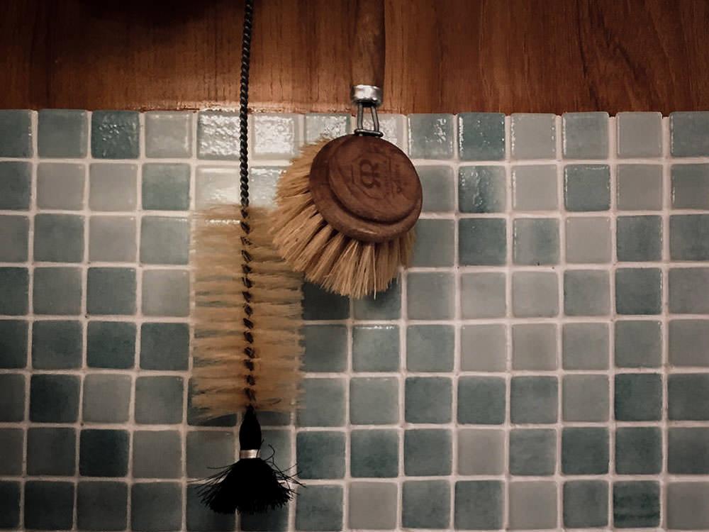 Zwei Spülbürsten hängen vor einer gefliesten Wand