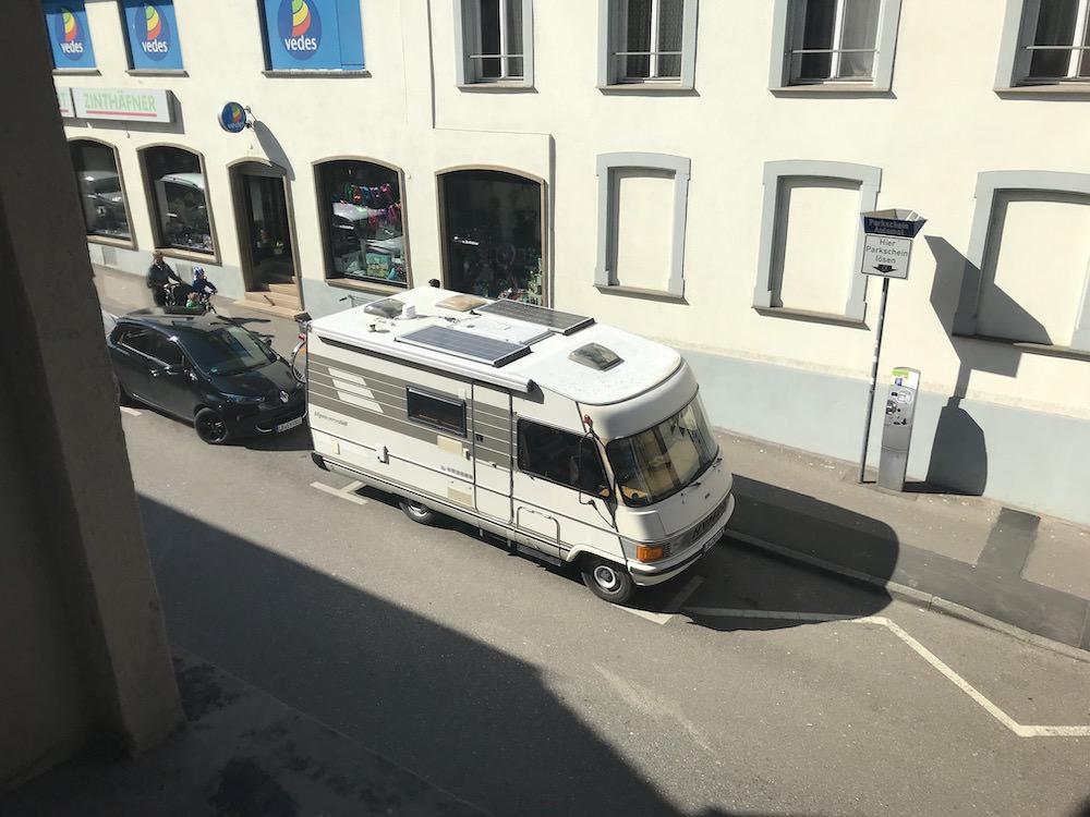 Unser Wohnmobil aus dem Fenster fotografiert, sodass man die Solaranlage auf dem Dach sehen kann.