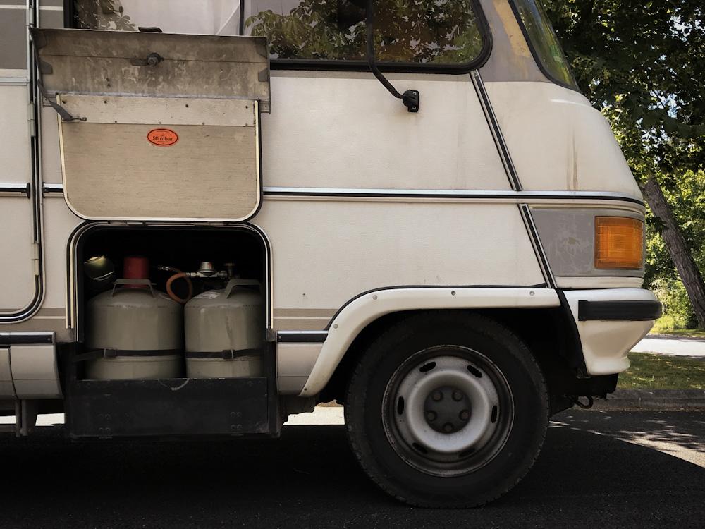 Ein offenes Gasfach eines Campers, in dem zwei Gasflaschen stehen