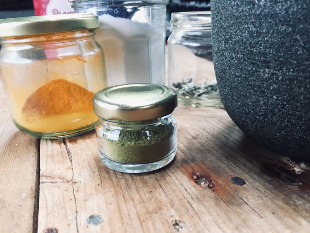 Körperpflege im Camper: Grünes Zahnputzpulver in einem kleinen Gläschen. Dahinter stehen Gläser mit Natron, Kurkuma und Salbei