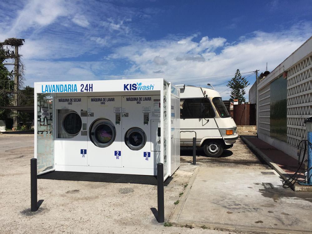 Das Wohnmobil parkt hinter einer öffentlichen Waschmaschine