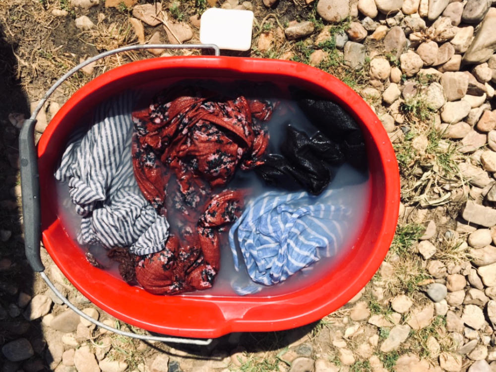 Wäsche waschen von Hand in einem Eimer